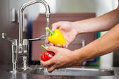 Kitchen porter washing pepper under running tap — Stock Photo