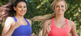 Two cute sporty women running in a park — Stock Photo