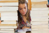 Concentrated pretty student studying between piles of books — Zdjęcie stockowe