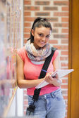 Pretty smiling student taking notes next to notice board — Stock Photo