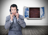 Frowning businessman wrapped in cables phoning — Stockfoto