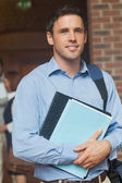 Attractive mature student posing in corridor holding some files — Stock Photo
