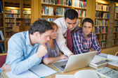 Mature students with teacher and laptop in library — Stok fotoğraf