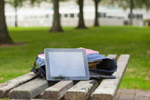 Purple schoolbag and tablet lying on park bench — Stock Photo