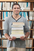 Adult student posing holding a stack of books — Stock Photo