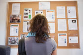 Student studying notice board — Stock Photo
