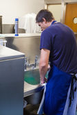 Kitchen porter standing behind sink — Stock Photo