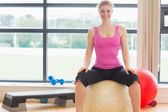 Beautiful woman sitting on exercise ball in fitness studio — Stock Photo