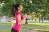 Pretty sporty woman jogging in a park — Stock Photo