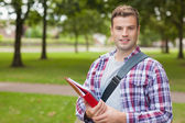 Handsome smiling student carrying folder — Stock Photo