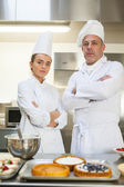 Frowning chef and head chef standing arms crossed — Stock Photo