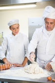 Serious head chef showing trainee how to prepare dough — Stock Photo