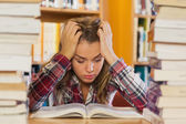 Irritated pretty student studying between piles of books — Stock Photo