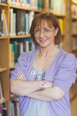 Mature female librarian posing in library with crossed arms — Stock Photo