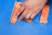 Close up of hand slicing raw salmon with sharp knife — Stock Photo