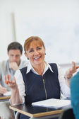 Amused female mature woman sitting in classroom — Stock Photo