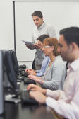 Teacher standing in front of computer class — Stock Photo