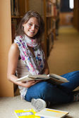 Smiling female student with books in the library aisle — Stock Photo