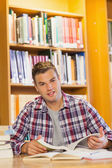 Handsome happy student studying his books — Stock Photo