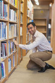Young attractive man cowering in front of bookshelves — Stock Photo