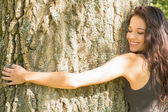 Casual happy brunette embracing a tree with closed eyes — Stock Photo