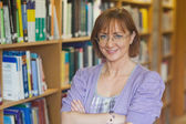 Mature intellectual woman posing in library — Stock Photo