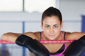 Beautiful young woman in black boxing gloves — Stock Photo