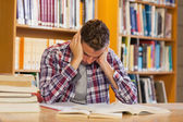 Handsome frustrated student studying his books — Stock Photo