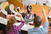 Students raising hands with teacher in the lecture hall — Stock Photo