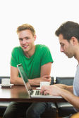 Students using laptop while having coffee at coffee shop — Stock Photo