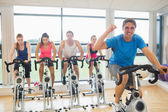 Happy man teaches spinning class to four people — Stok fotoğraf