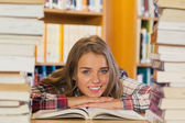 Smiling pretty student studying between piles of books — Stock Photo