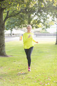 Active smiling blonde jogging towards camera — Stock Photo