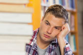 Exhausted handsome student studying between piles of books — Stockfoto
