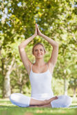 Cheerful smiling woman meditating with hands raised in prayer — Stock Photo