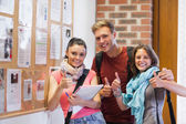 Three smiling students standing next to notice board showing thu — Stock Photo
