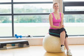 Cheerful woman sitting on exercise ball in fitness studio — Stock Photo