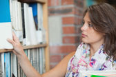 Gemale student selecting book from the shelf in library — Stock Photo