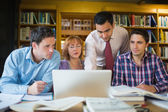 Mature students with teacher and laptop in library — Foto de Stock