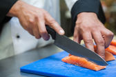 Close up of chef slicing salmon with sharp knife — Stock Photo
