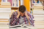 Concentrated handsome student studying between piles of books — Stok fotoğraf