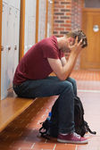 Upset handsome student holding his head — Stock Photo