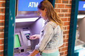 Pretty brunette student withdrawing cash — Stock Photo