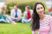Smiling young college student with blurred friends in park — Stock Photo