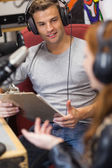 Attractive radio host interviewing a guest holding clipboard — Stock Photo