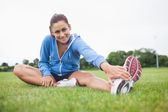 Portrait of a sporty stretching her leg on the grass — Stock Photo