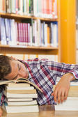 Exhausted handsome student resting head on piles of books — Stock Photo