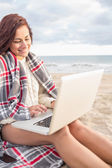 Woman covered with blanket using laptop at beach — Stock Photo