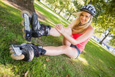 Casual cheerful blonde wearing roller blades and helmet — Stock Photo