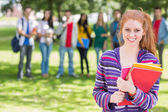 College girl holding books with students in park — Stock Photo